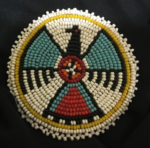 Thunderbird Beaded Rosette with Yellow Border Lakota culture 20th century Glass beads, cloth, and leather, L. 7.7 cm x W. 5 mm x H. 7.5cm Ralph Foster Museum collection #90.42.20