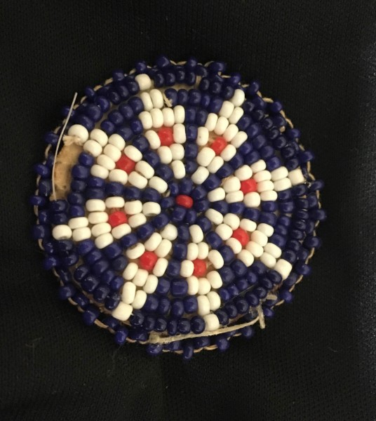 Purple and White Flower Beaded Rosette Apache culture (?) 20th century Glass beads, cloth, and leather, L. 4 cm x W. 5 mm x H. 4 cm Ralph Foster Museum collection #NN012