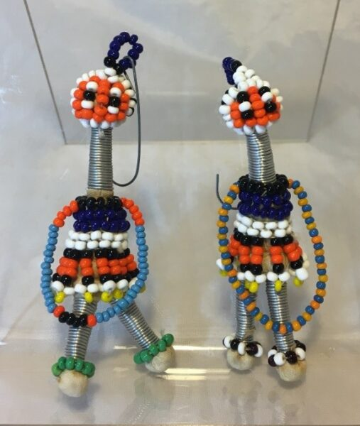 Image of a pair of bead and wire girl figures