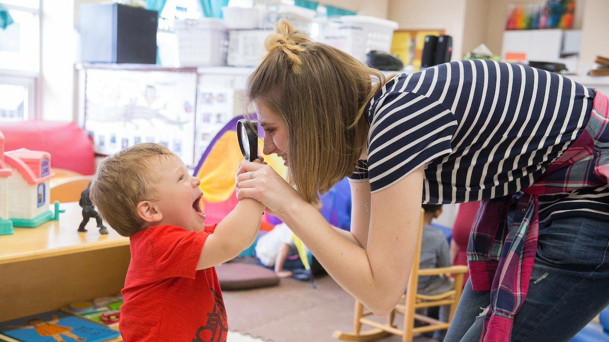 A teacher works with a young child