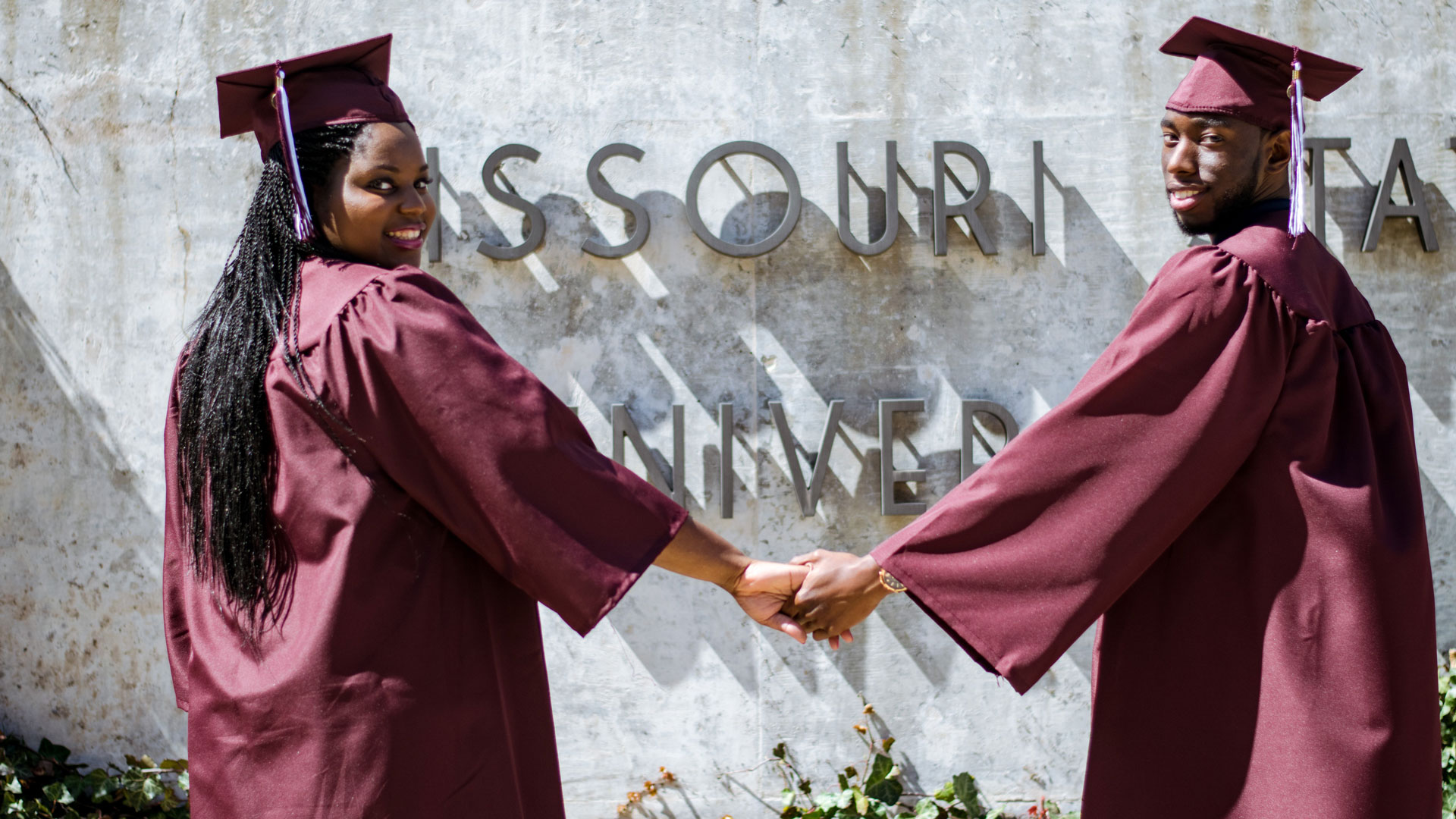 Alumni in graduation gowns in front of Missouri State sign