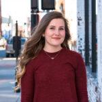 Alexis Stegner poses on a city sidewalk, smiling