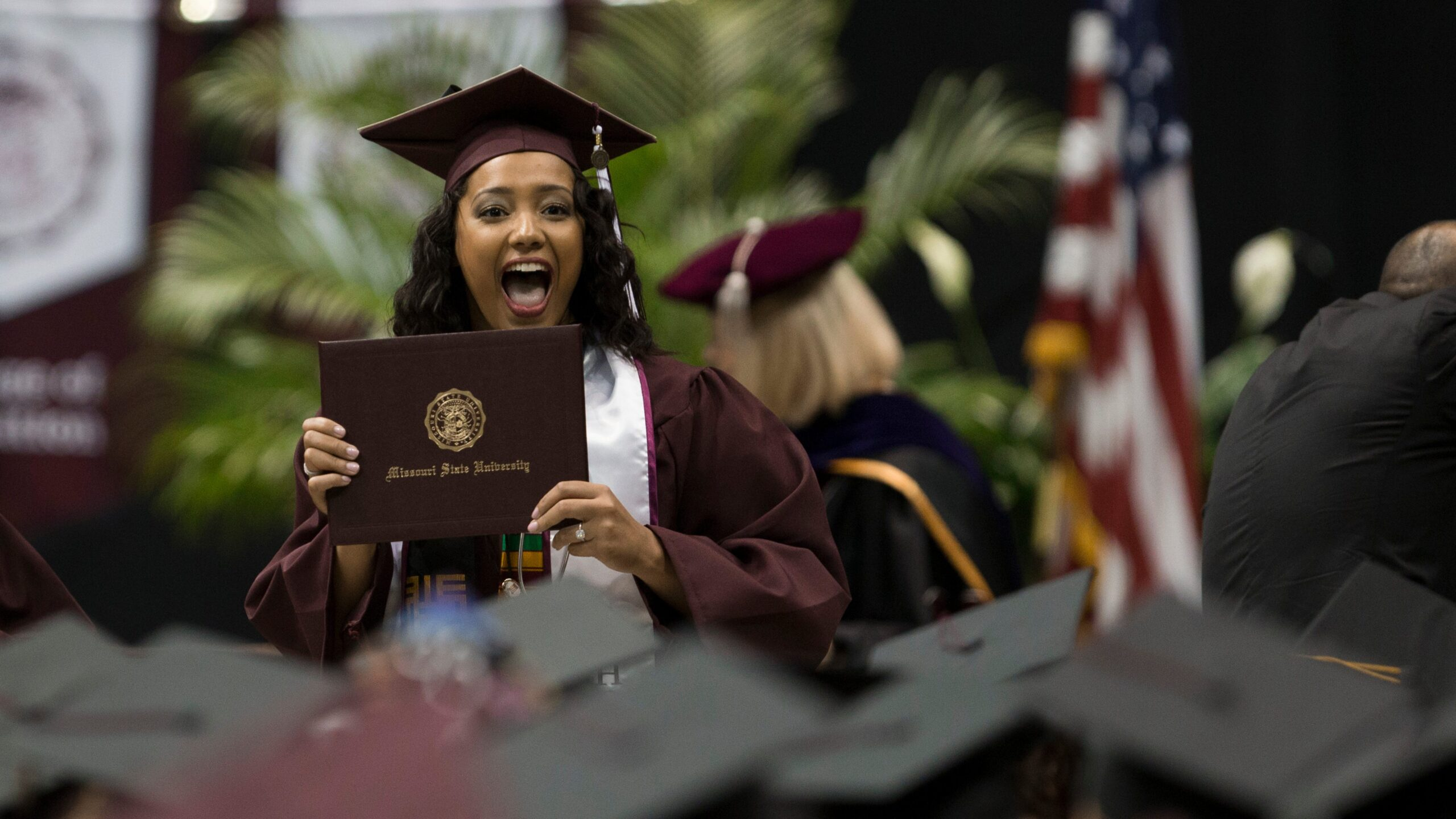 Among a sea of graduate hats, a woman holds her diploma excitedly.