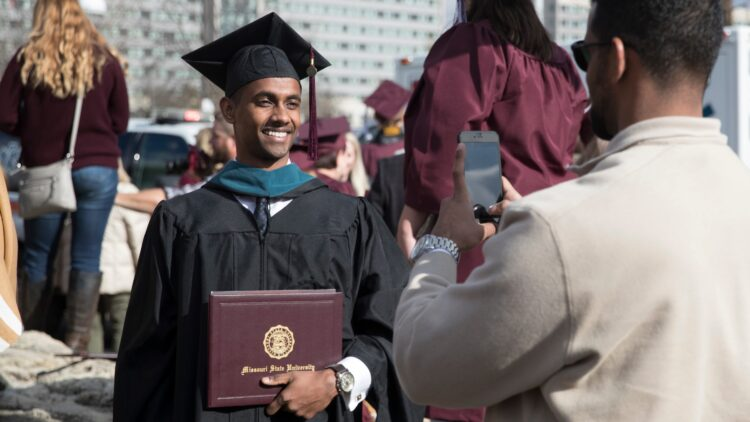 A graduate holds his diploma close while a friend snaps a picture.