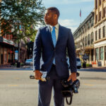 Bryant Clerkley stands in a street with his camera and microphone.