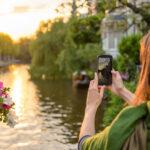 woman holding camera phone up at river