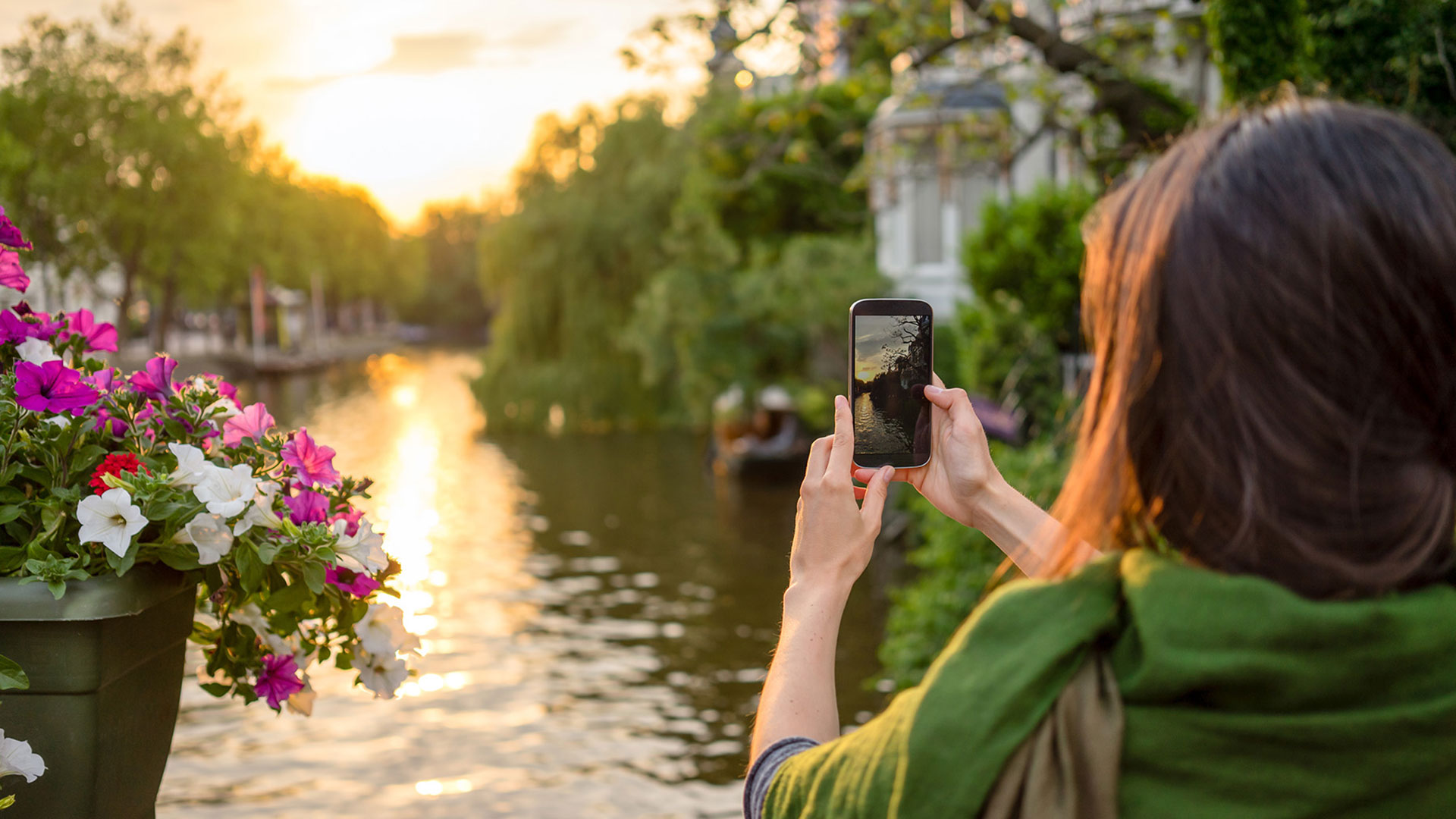 woman holding camera phone up at river