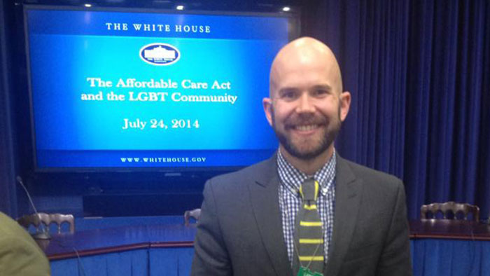 Andrew in front of slide about White House Affordable Care Act and LGBT