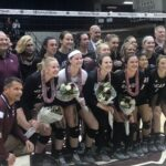 Senior volleyball players with flowers and coaches posing in front of a net