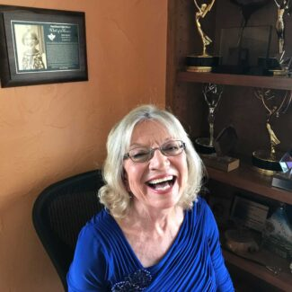 Kay Nelson smiling in front of her awards