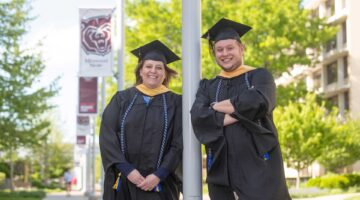 Jayma and Ethan Porter standing in their graduation gowns on campus