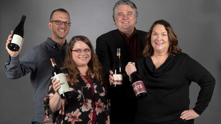 Hospitality Leadership Committee holding up wine bottles