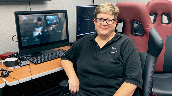 Dr. Deborah Larson seated at an editing bay in Strong Hall control room.