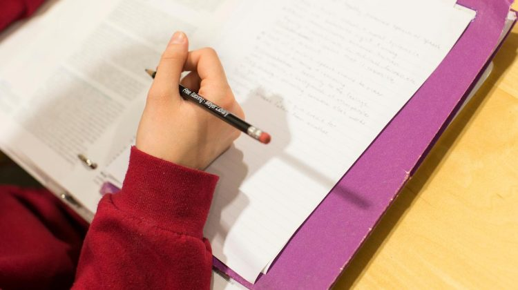 Student writes in a notebook