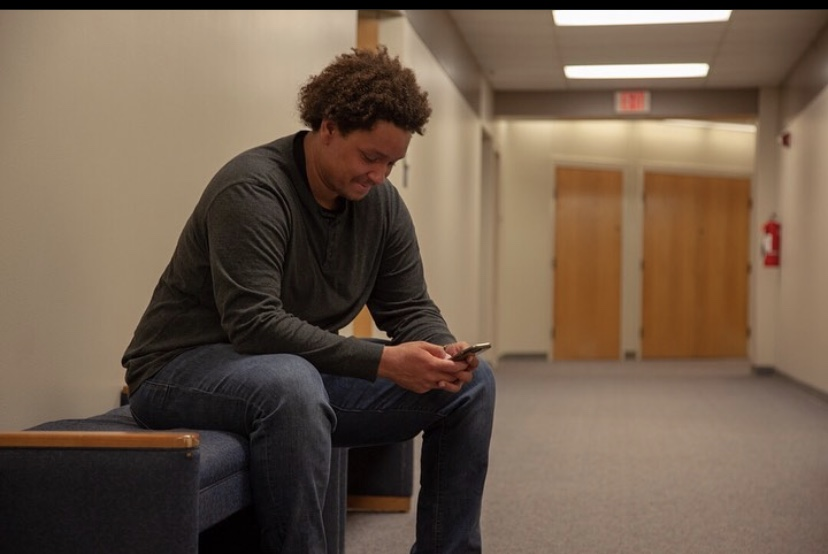 Michael sits on a bench in a hallway looking at his phone