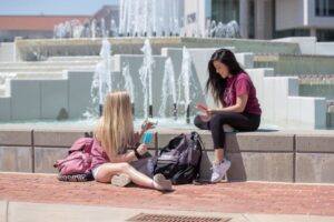 Two students studying at the fountain while holding popsicles