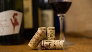 Wine corks with a wine glass and wine bottles in the background.