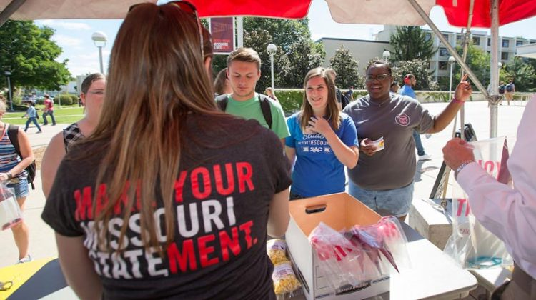 A staff member wearing a Make Your Missouri Statement T-shirt hands out swag to students