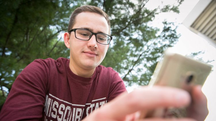 A male student in a maroon shirt uses his iPhone.