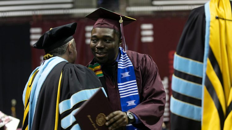 A graduate shakes hands with a faculty member at commencement.
