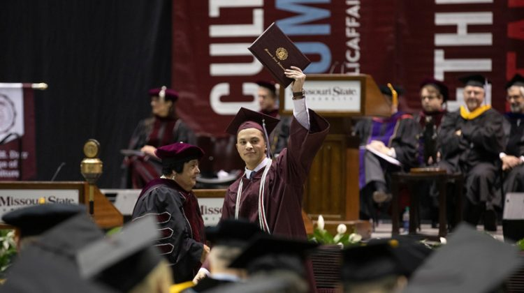 A graduate proudly holds up his maroon diploma cover.