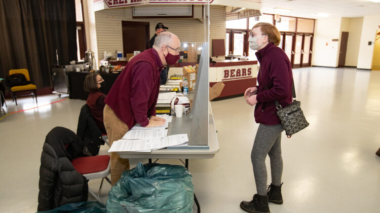 President Smart assists with student check-in for COVID testing.