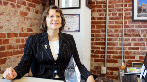 Dr. Follensbee sits at her office desk behind her service-learning award