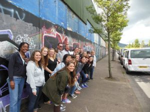 "The class visits the ""Peace Wall"" that separates the Catholic and Protestant communities in Belfast."