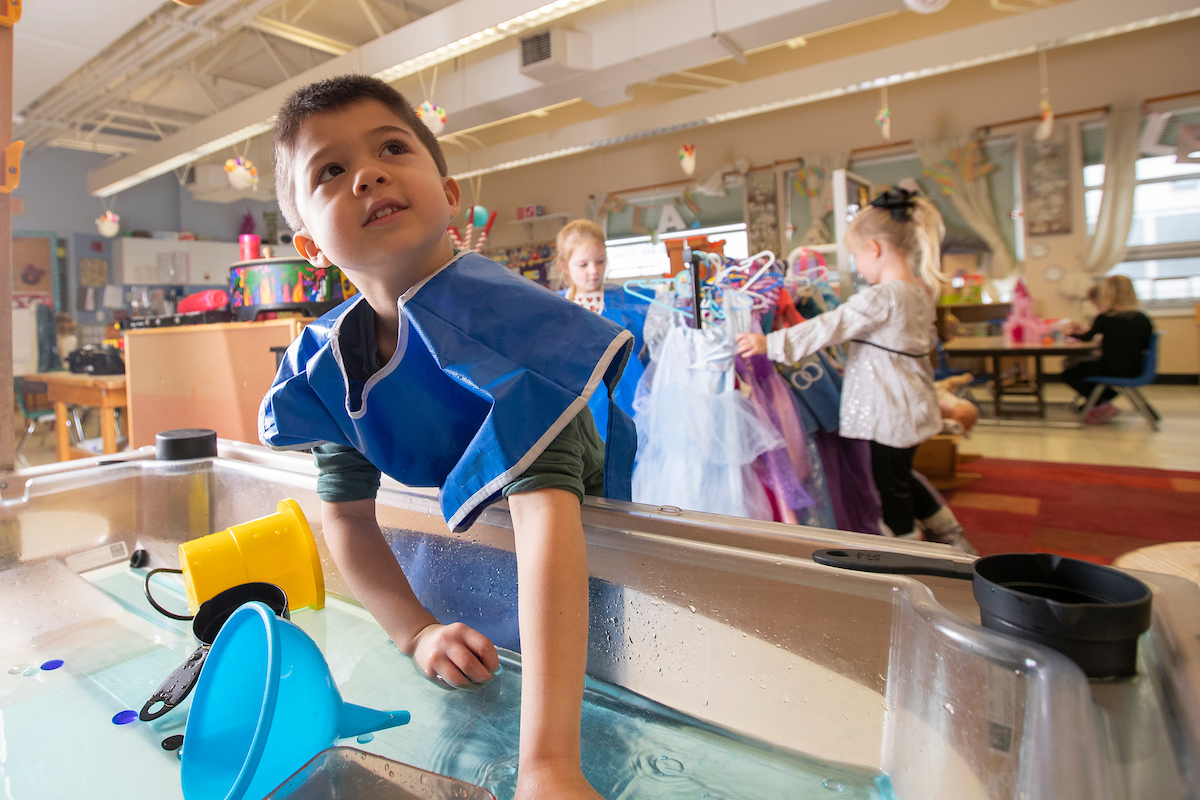 A young boy looks up from playing with toys in a tub of water.