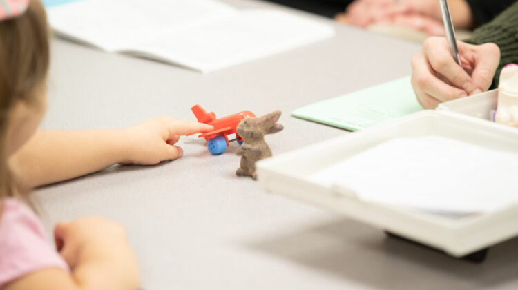 Preschool student points to toy plane.