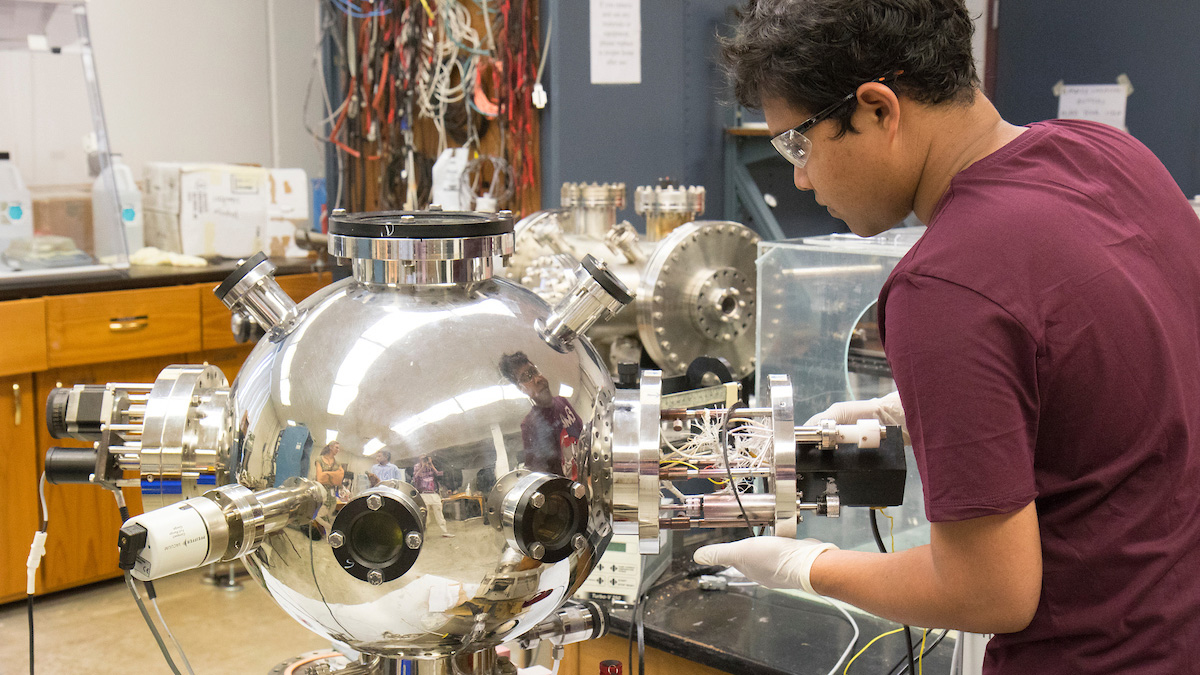 Graduate students and Dr. Kartik Ghosh work with pulsed laser deposition. Pictured, graduate student Mahmud Reaz.