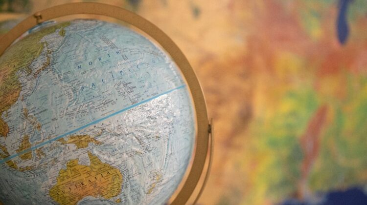 A globe rests in front of a geography map.