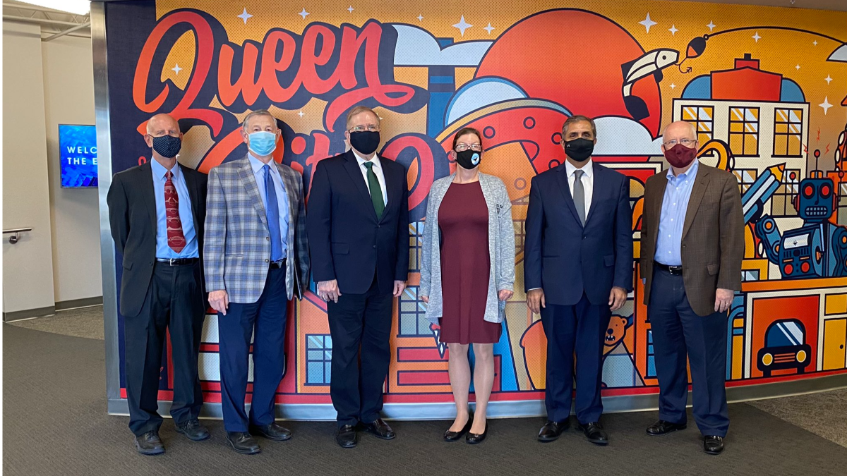 Chancellor meeting attendees pose in front of Queen City mural wall.