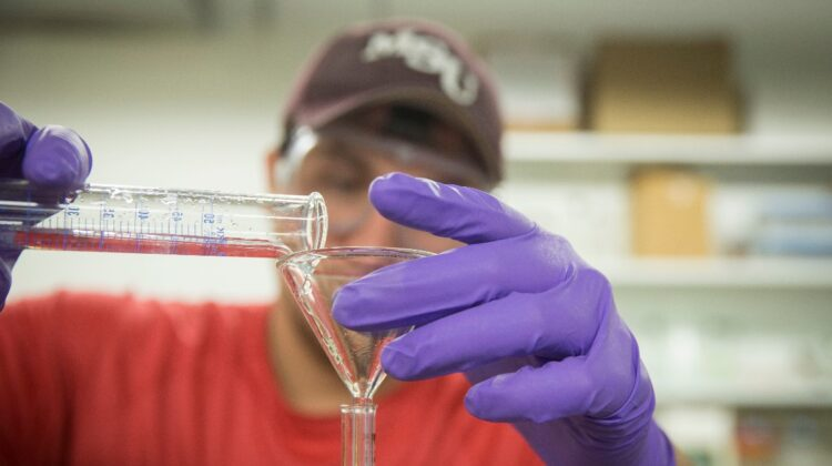 A student pours solution into cylinder in lab. from break through