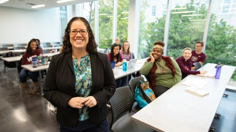 Dr. Liza Cobos stands at head of classroom in front of tables. Adoring students smile at her from these tables.