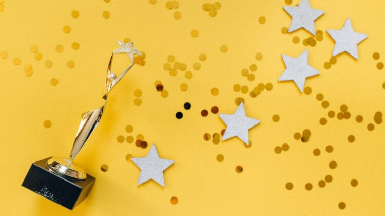 An award rests among star cut outs and glitter on a bright yellow backdrop.
