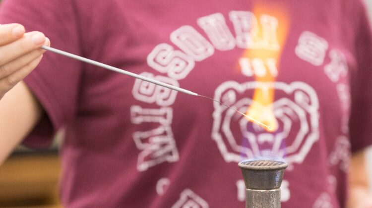 A female student in a Missouri State University T-shirt operates a burner.