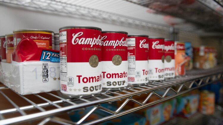A row of soup cans rests on a storage shelf.