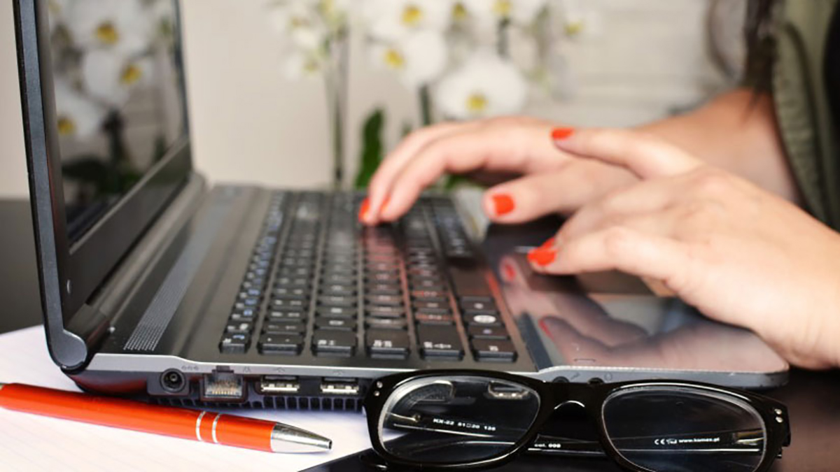 A woman types on the keyboard of her laptop.