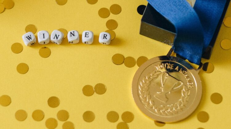"""A medal and beads spelling """"winner"""" rest on yellow backdrop surrounded by glitter. Photo by Nataliya Vaitkevich from Pexels."""