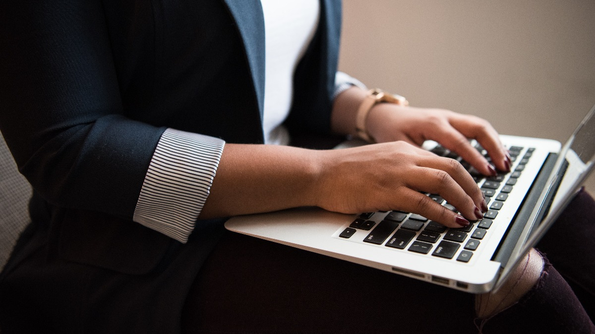 A young woman wearing a blazer types on the keyboard of her laptop. Photo by Christina Morillo from Pexels.