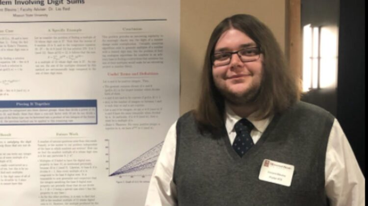 Vincent Blevins with research poster at mathematics conference.