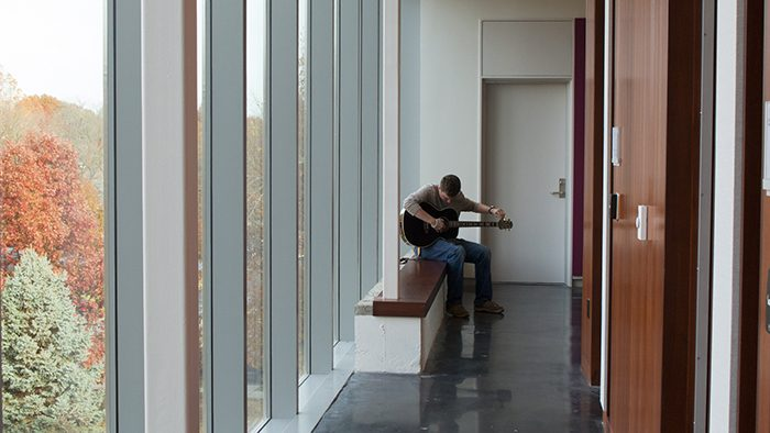 Student playing guitar in Ellis Hall