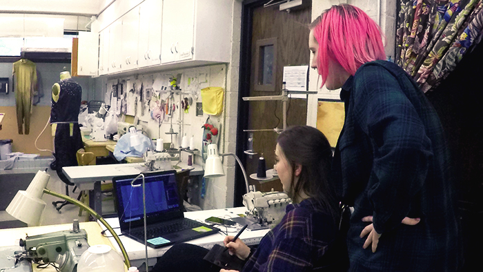 Costume shop manager reviews the digital design renderings of DTSM senior.