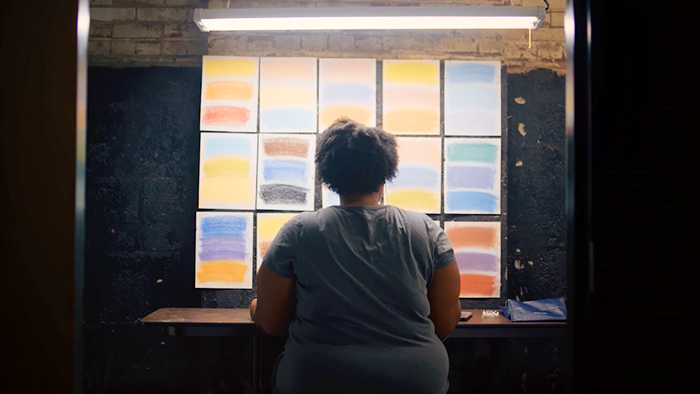 "Still from promotional video ""Take Your Shot,"" showing a student artist seated in front of several pastel color palettes"