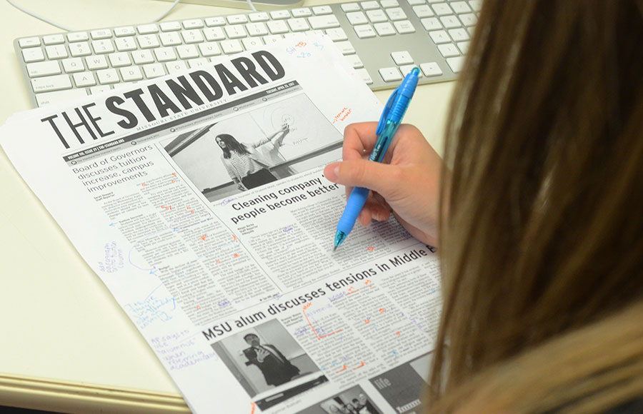 A copy editor reviews a proof of The Standard
