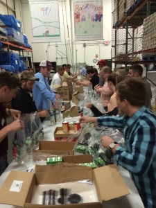 students stand at tables packing food in boxes