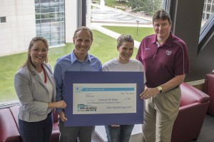Recent MSU alum Sarah Moore and Prof. Clark (right) present the check to Convoy representatives Jaimie Trussell and Adam Riso (left).