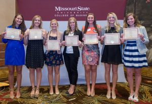 A group of students pose with their scholarship certificates