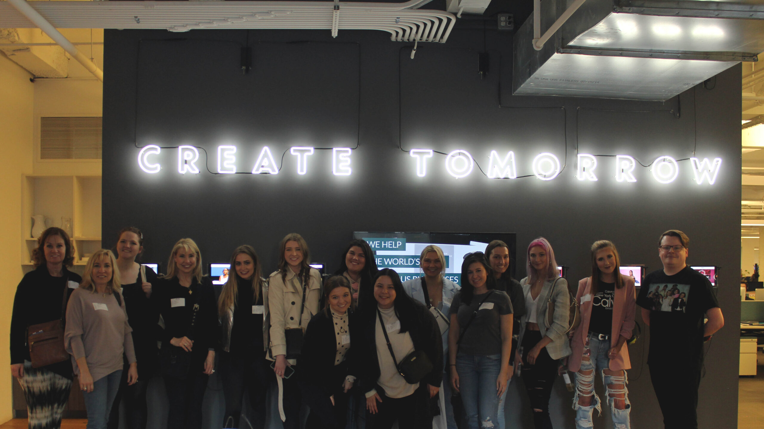 """Group of students under a neon sign that reads, """"Create Tomorrow."""""""